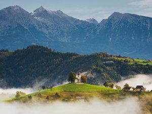 CALVENDO Puzzle Kirche St. Thomas vor Bergen, umgeben von Nebel